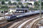blau/145234/110-254-0-steht-mit-einem-d-zug 110 254-0 steht mit einem D-Zug in der Abstellgruppe, im Bw Ulm befinden sich weitere 110.1, 140 und 150, am 24.07.1983.